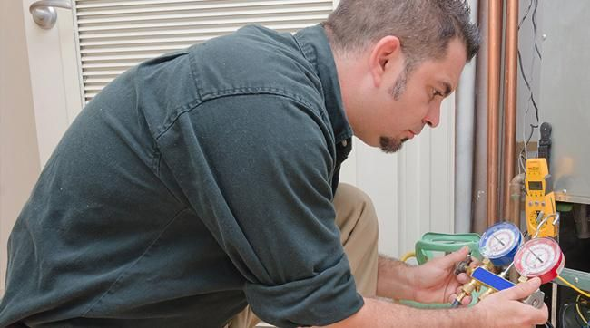hvac technician doing repair of air conditioner