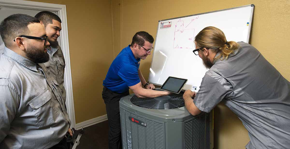 AC technicians at Tiger Heating & Air with air conditioner in Corpus Christi HVAC shop