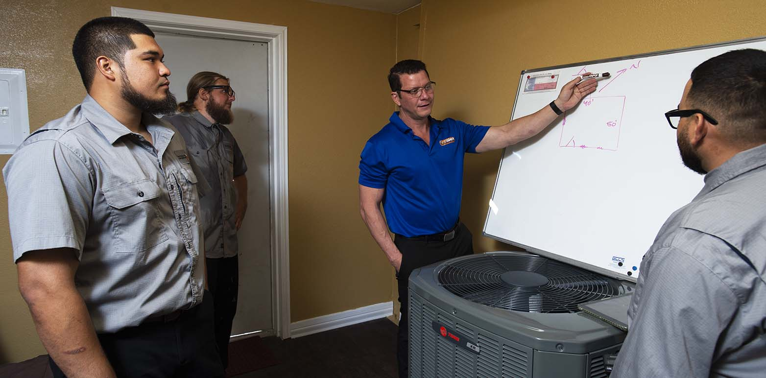 Tiger Heating & Air AC technicians studying SEER rating at Corpus Christi shop